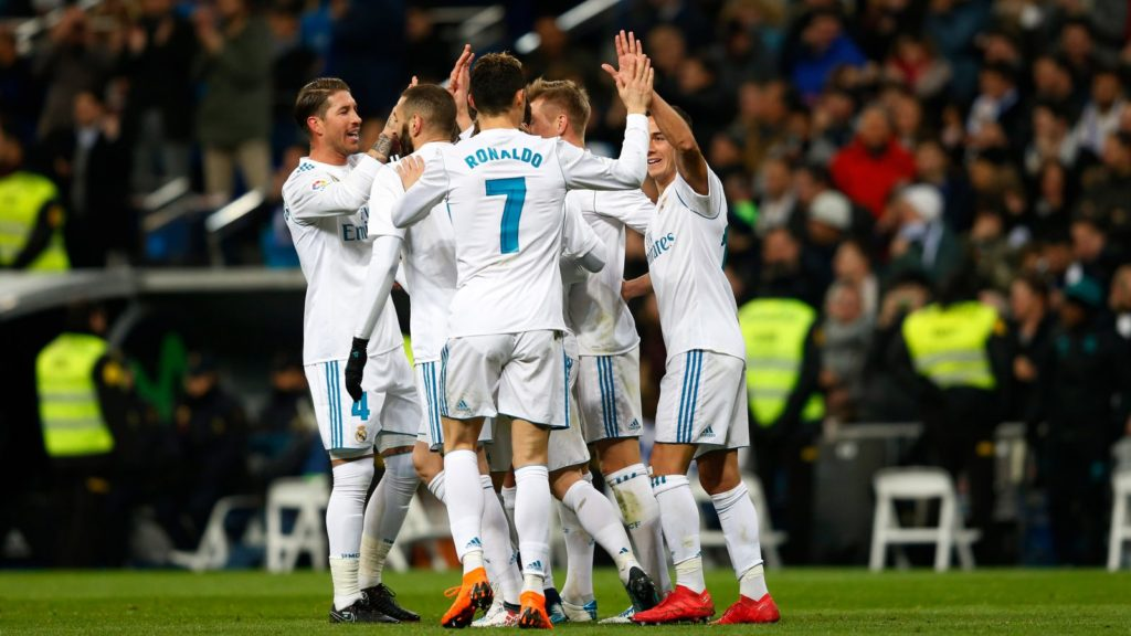 The Real Madrid team high-fiving each other in a soccer game